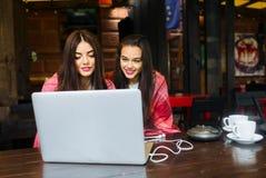 2 девушки наблюдая что-то в компьтер-книжке Стоковая Фотография RF