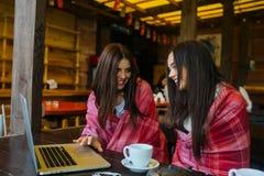 2 девушки наблюдая что-то в компьтер-книжке Стоковые Фотографии RF