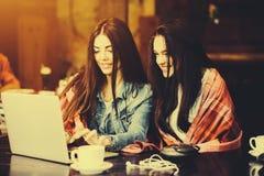 2 девушки наблюдая что-то в компьтер-книжке Стоковые Изображения