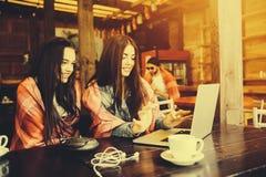 2 девушки наблюдая что-то в компьтер-книжке Стоковое Изображение
