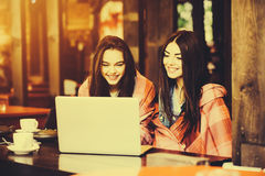 2 девушки наблюдая что-то в компьтер-книжке Стоковое Фото