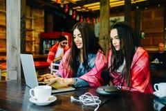 2 девушки наблюдая что-то в компьтер-книжке Стоковая Фотография