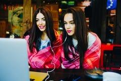 2 девушки наблюдая что-то в компьтер-книжке Стоковые Изображения RF