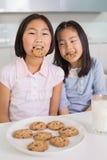 2 девушки наслаждаясь печеньями и молоком в кухне Стоковое фото RF