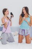 2 девушки на кровати поя в их щетки для волос Стоковое Изображение