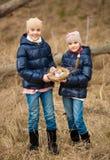 2 девушки на охоте пасхального яйца на лесе Стоковые Изображения