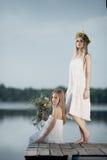 2 девушки на побережье на пристани Стоковые Изображения RF