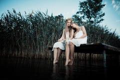2 девушки на побережье на пристани Стоковые Фото