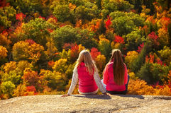 2 девушки на пропасти скалы обозревая лес осени Стоковое Фото