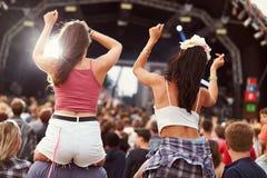 2 девушки на плечах в толпе на музыкальном фестивале стоковые изображения rf
