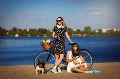 2 девушки на пляже с велосипедом и французскими бульдогами Стоковые Изображения RF