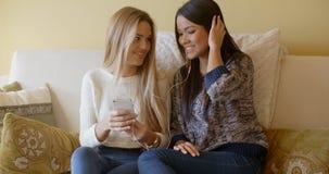 2 девушки на софе слушают к музыке Стоковое Изображение RF