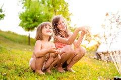 2 девушки на спринклере, солнечном лете в саде Стоковые Фотографии RF