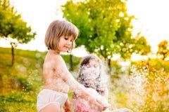 2 девушки на спринклере, солнечном лете в саде Стоковое Изображение