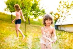 2 девушки на спринклере, солнечном лете в саде Стоковые Изображения