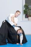 2 девушки на тренировке айкидо на белой предпосылке Стоковые Изображения
