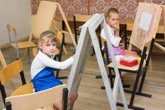 2 девушки на уроке чертежа слушают к объяснениям учителя Стоковые Фотографии RF