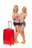 2 девушки нося джинсы замыкают накоротко с большим красным чемоданом Стоковое Изображение RF