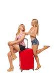 2 девушки нося джинсы замыкают накоротко с большим красным чемоданом Стоковое Фото