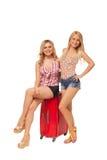 2 девушки нося джинсы замыкают накоротко с большим красным чемоданом Стоковое фото RF