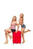 2 девушки нося джинсы замыкают накоротко с большим красным чемоданом Стоковая Фотография RF