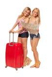2 девушки нося джинсы замыкают накоротко с картой и красным чемоданом Стоковая Фотография RF