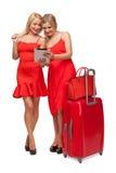 2 девушки нося красный цвет одевают с большими чемоданом и сумкой и tabl Стоковая Фотография RF