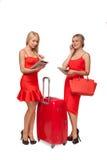 2 девушки нося красный цвет одевают с большими чемоданом и сумкой и tabl Стоковые Изображения