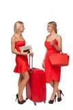 2 девушки нося красный цвет одевают с большими чемоданом и сумкой Стоковое Изображение RF