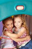 2 девушки обнимая в детском саде Стоковое фото RF