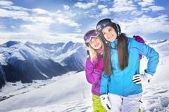 2 девушки обнимая в небе лыжного курорта зимы голубом Стоковое Изображение RF