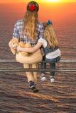 2 девушки обнимая сидеть на луче Стоковые Изображения RF
