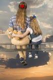 2 девушки обнимая сидеть на луче Стоковое Фото