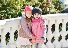 2 девушки обнимая outdoors Стоковые Фотографии RF