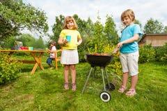 2 девушки около гриля делая BBQ в саде Стоковое Изображение