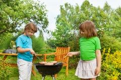 2 девушки около мяса приготовления на гриле BBQ в саде Стоковая Фотография RF