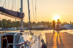 2 девушки около яхты на заходе солнца Стоковое Изображение
