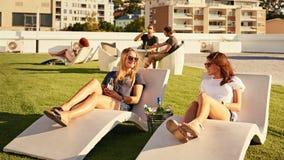 2 девушки ослабляя пока кладущ на sunbeds в солнце Стоковые Изображения RF