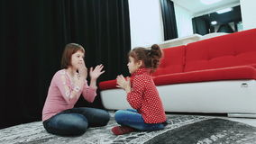2 девушки, одного из их с Синдромом Дауна, сидя на ковре дома, игра и имеют потеху сток-видео
