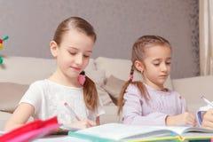 2 девушки пишут в их ученических книгах Стоковые Изображения RF