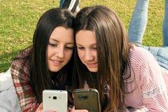 2 девушки пишут в мобильных телефонах Стоковое Фото