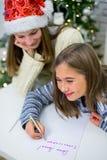 2 девушки пишут письмо к Санта Клаусу Стоковые Фотографии RF