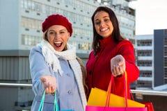 2 девушки показывая их хозяйственные сумки Стоковые Изображения