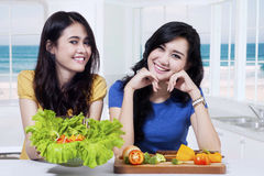 2 девушки показывая овощам салат Стоковая Фотография RF