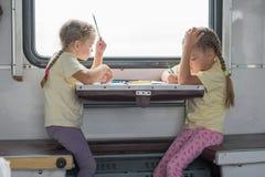 2 девушки покрашенной для бортовой таблицы в второго класса экипаже поезда Стоковая Фотография