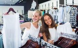 2 девушки покупая верхние части в магазине одежд Стоковые Фотографии RF