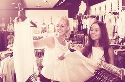 2 девушки покупая верхние части в магазине одежд Стоковое фото RF