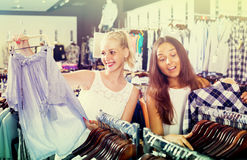 2 девушки покупая верхние части в магазине одежд Стоковое Изображение RF