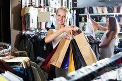 2 девушки покупая верхние части в магазине одежд Стоковое Изображение