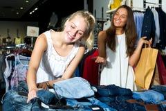 2 девушки покупая верхние части в магазине одежд Стоковое Фото